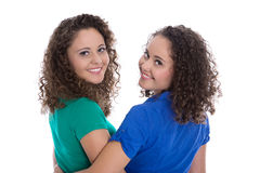 Portrait of an isolated couple of real twin sisters over white w Stock Photos