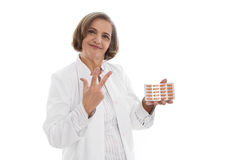 Portrait: isolated older doctor holding medicine making three fi. Nger symbol Royalty Free Stock Image
