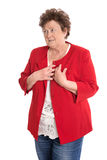 Portrait: Isolated older woman in red has heart problems. Royalty Free Stock Photos