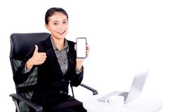 Portrait isolated Southeast Asian business woman wears dark gray suit is looking at the camera also show her mobile phone on white stock images