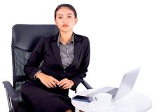 Portrait isolated Southeast Asian business woman wears dark gray suit is looking at the camera and sitting on chair with office stock photography
