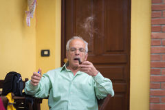 Portrait of italian senior man smoking pipe. And looking at the camera. Outdoor setting, house door and wall background Royalty Free Stock Photo