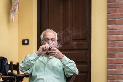 Portrait of italian senior man smoking pipe. And looking at the camera. Outdoor setting, house door and wall background Stock Photos