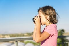 Portrait of a ittle girl taking photographs outdoors. Portrait of a ittle girl with a pink shirt taking photographs outdoors royalty free stock photos