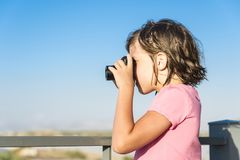 Portrait of a ittle girl taking photographs outdoors. Portrait of a ittle girl with a pink shirt taking photographs outdoors stock photo