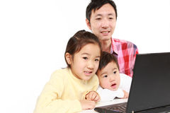 Portrait of Japanese father and children on laptop computer Royalty Free Stock Photo