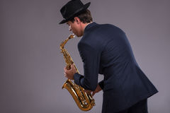 Portrait of a jazz man in a suit with a hat hiding Stock Photos