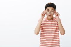 Portrait jeune de l'étudiant masculin asiatique mignon étonné et stupéfait enlevant des verres en tant qu'audition des actualités images stock