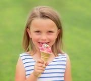 Portrait jeunes des années blondes adorables et belles de la fille 6 ou 7 mangeant heureux de sourire délicieux de crème glacée d Photo libre de droits
