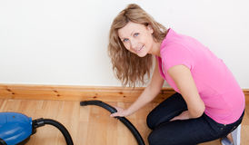 Portrait of a jolly woman vacuuming Stock Image