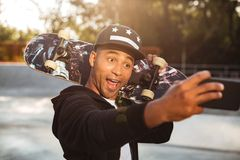 Portrait of a joyful african male teenager. Taking a selfie while holding a skateboard on his shoulders outdoors Royalty Free Stock Images