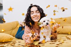 Portrait joyful amazing young woman smiling with closed eyes in falling golden tinsels. Chilling on couch with home pets. Little white dog, smiling, cheerful royalty free stock photo