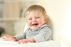 Joyful baby with his first teeth looking at you. Portrait of a joyful baby with his first teeth looking at you sitting on a high chair Royalty Free Stock Photos