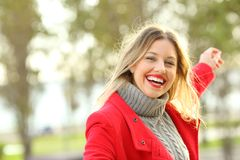 Joyful beauty woman carefree in winter. Portrait of a joyful beauty woman with perfect smile dancing carefree outdoors in a park in winter with copy space at stock image