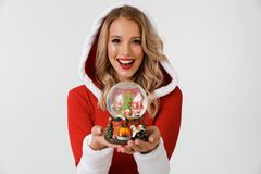 Portrait of a joyful blonde woman. Dressed in red New Year costume standing over white background, holding snowball stock photography