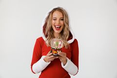 Portrait of a joyful blonde woman. Dressed in red New Year costume standing over white background, holding snowball, winking royalty free stock photos