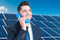 Portrait of joyful business man talking on telephone. In solar power station as futuristic ecological power concept Stock Photos