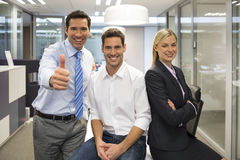 Portrait of joyful business team, man showing thumb up. Woman men desk smiling business office looking camera Stock Photo