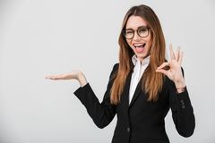 Portrait of a joyful businesswoman. Dressed in suit showing ok gesture and holding copy space on her palm isolated over gray background Royalty Free Stock Photo