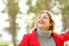 Candid girl joking happy in a park. Portrait of a joyful candid girl wearing a red jacket and a sweater joking outdoors in a park in winter Royalty Free Stock Images
