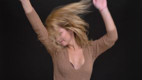Portrait of joyful caucasian long-haired woman dancing strangely into camera on black background. Portrait of joyful caucasian long-haired woman dancing stock footage