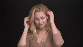 Portrait of joyful caucasian long-haired woman in earphones joyfully dancing to music on black background. Portrait of joyful caucasian long-haired woman in stock video