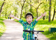 Portrait of a joyful child on a bicycle in a summer park Royalty Free Stock Photo