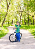 Portrait of a joyful child on a bicycle in a summer park Royalty Free Stock Photos