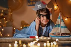 Smiling kid playing in pirate game. Portrait of joyful child lying on the floor with toy ship and dreaming being buccaneer. Concept fantasy and childhood royalty free stock photography