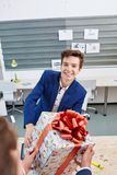 Portrait of joyful colleagues giving xmas presents to each other. Holiday concept. Attractive men smiling and giving xmas presents to colleaguaes. Smilling Royalty Free Stock Photography