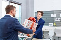 Portrait of joyful colleagues giving xmas presents to each other. Holiday concept. Attractive men smiling and giving xmas presents to colleaguaes. Smilling Royalty Free Stock Photos