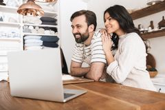 Portrait of joyful couple looking at laptop while cooking pastry in kitchen at home. Portrait of joyful couple men and women 30s wearing aprons looking at laptop royalty free stock photos