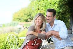 Portrait of joyful couple sitting in garden Stock Photos