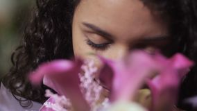 Portrait of joyful female smelling floral bouquet. Close up portrait of cute curly mixed race woman floral artist sniffing wonderful flower smell of floral bunch stock footage