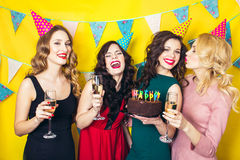 Portrait of joyful friends toasting and looking at camera at birthday party.Smiling girls with glasses of champagne. Portrait of joyful friends toasting and Royalty Free Stock Photos