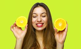Portrait of joyful funny pretty cheerful girl having two pieces of orange with close eyes isolated on yellow background stock photography