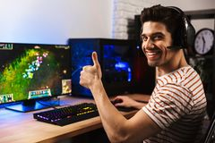 Portrait of joyful gamer guy in headphones playing video games o. N computer and showing thumb up stock photos