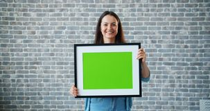 Portrait of joyful girl carrying green screen picture on brick wall background. Portrait of joyful girl carrying mock-up green screen picture on brick wall stock video