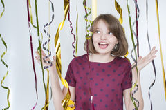 Portrait of joyful girl among multicolored ribbons. Stock Images
