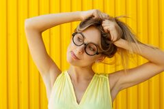 Portrait of a joyful girl wearing toy funny glasses over yellow stock photography