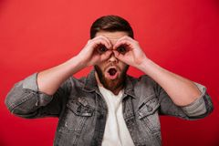 Portrait of joyful guy 30s in jeans jacket having fun and lookin. G on camera through holes like binoculars  over red background Royalty Free Stock Photo