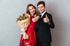 Portrait of a joyful happy couple holding flower bouquet Royalty Free Stock Image