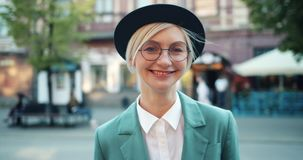 Portrait of joyful hipster in glasses and hat smiling standing outdoors alone. Portrait of joyful hipster attractive blonde in glasses and hat smiling standing stock video