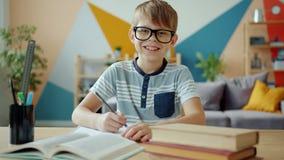 Portrait of joyful kid smiling laughing looking at camera doing homework indoors
