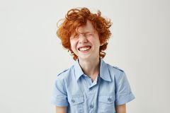 Portrait of joyful little boy with ginger hair and freckles laughing out loud with closed eyes in classroom during break.  royalty free stock photos