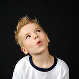 Portrait of joyful little boy. Happy boy making a funny face on a black background Royalty Free Stock Image