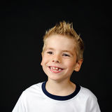Portrait of joyful little boy. Happy boy making a funny face on a black background Stock Photos