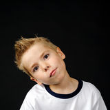 Portrait of joyful little boy. Happy boy making a funny face on a black background Stock Photography
