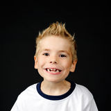 Portrait of  joyful  little boy. Happy boy making a funny face on a black background Royalty Free Stock Photography