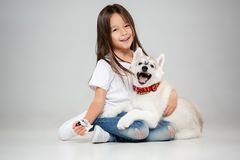 Portrait of a joyful little girl having fun with siberian husky puppy on the floor at studio royalty free stock photos